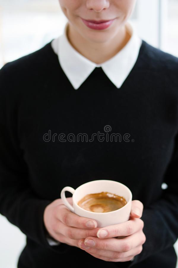 Chica joven del adicto al café que lleva a cabo la bebida caliente de la taza foto de archivo libre de regalías