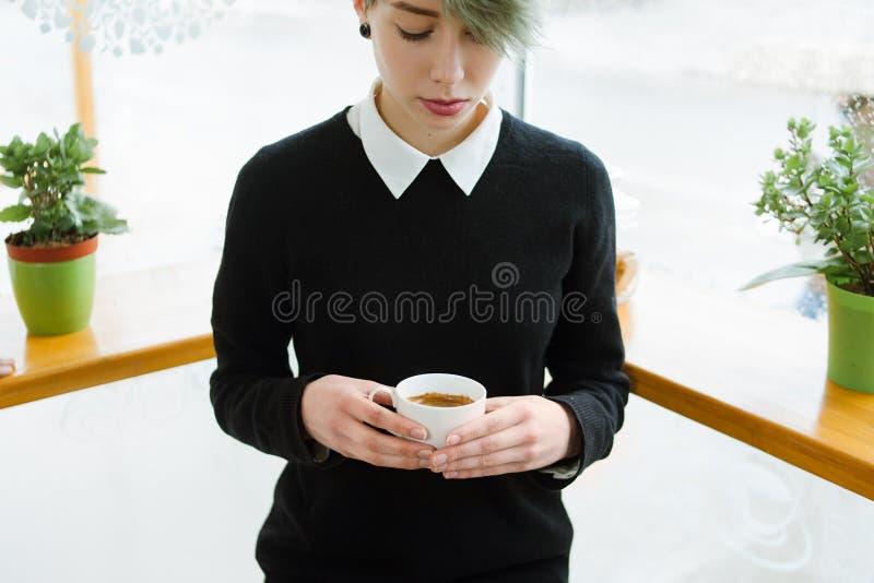 Chica joven del adicto al café que lleva a cabo la bebida caliente de la taza fotos de archivo