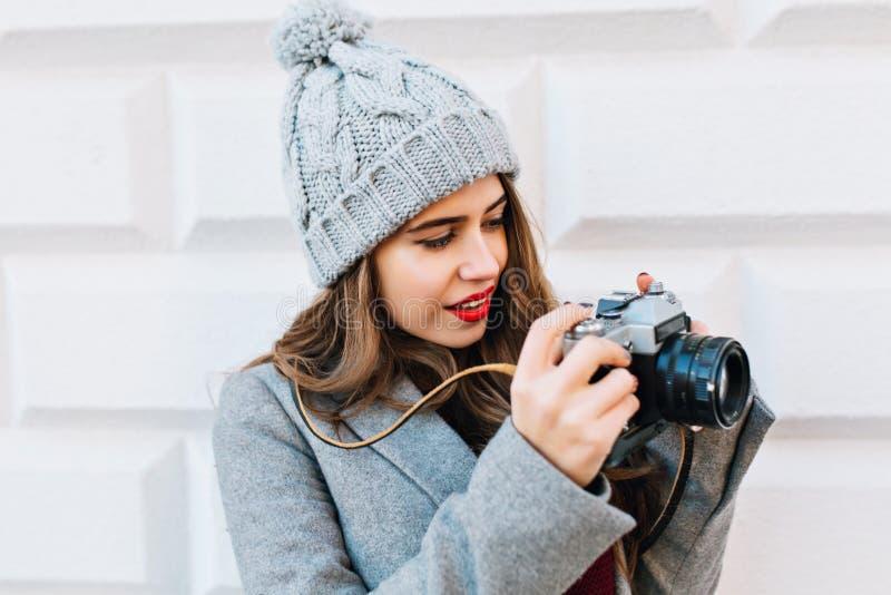 Chica joven del retrato del primer con el pelo largo en capa gris en el fondo gris de la pared al aire libre Adentro la considera foto de archivo libre de regalías