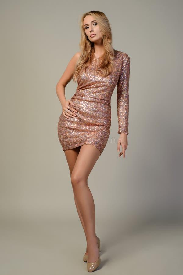 Chica joven delgada en vestido brillante rosado elegante imagenes de archivo