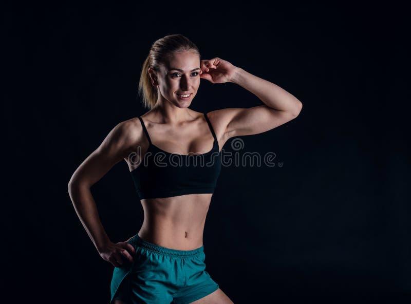 Chica joven deportiva en la ropa de deportes que muestra los músculos en fondo negro Mujer atlética joven bronceada Un cuerpo fem imagenes de archivo