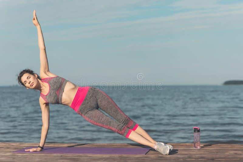 Chica joven deportiva por la mañana en el embarcadero en la costa, yoga practicante La mujer hace la gimnasia al aire libre Salud imagenes de archivo