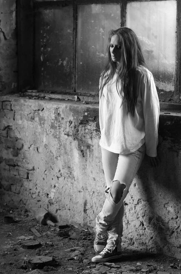 Chica joven deprimida que se coloca en el edificio abandonado imagenes de archivo