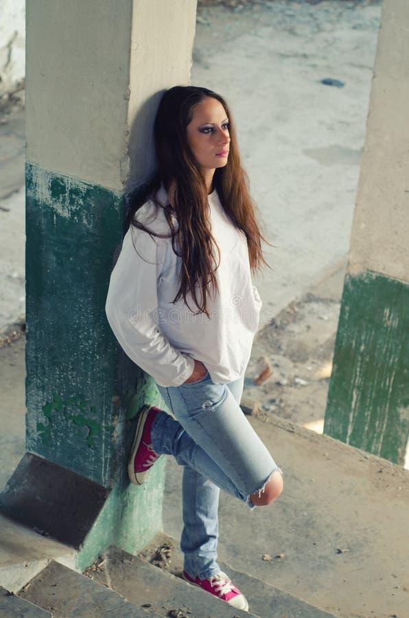 Chica joven deprimida que se coloca en las escaleras concretas fotografía de archivo libre de regalías