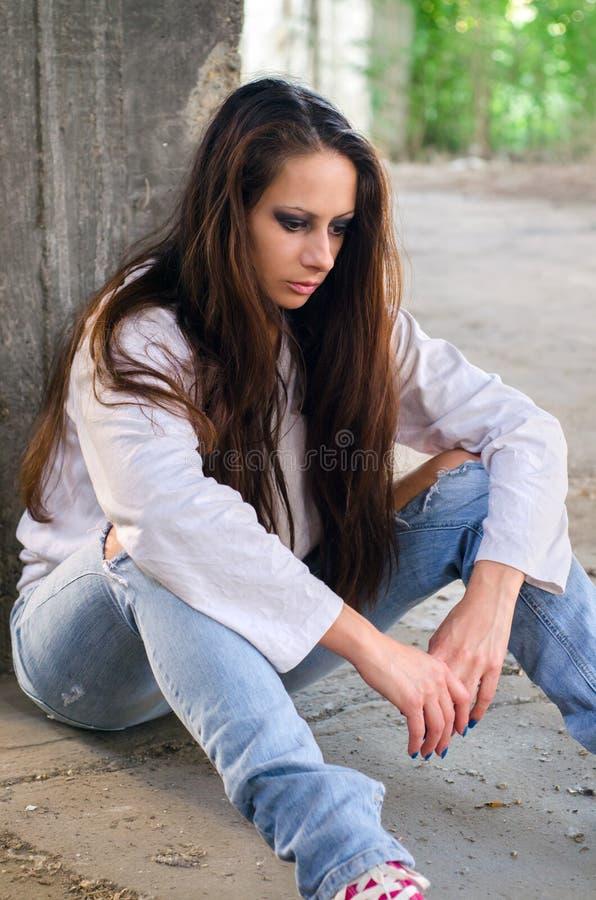 Chica joven deprimida que se sienta en el piso concreto imágenes de archivo libres de regalías