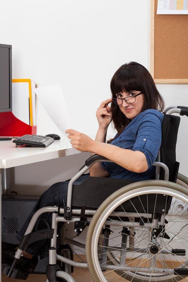 Chica joven discapacitada en la silla de ruedas que trabaja en su oficina imagen de archivo