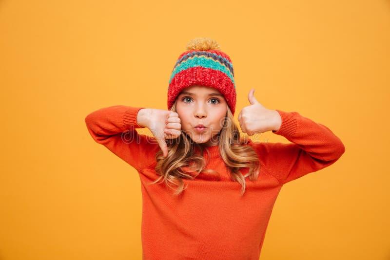 Chica joven divertida en el sombrero que muestra el pulgar hacia arriba y hacia abajo imágenes de archivo libres de regalías