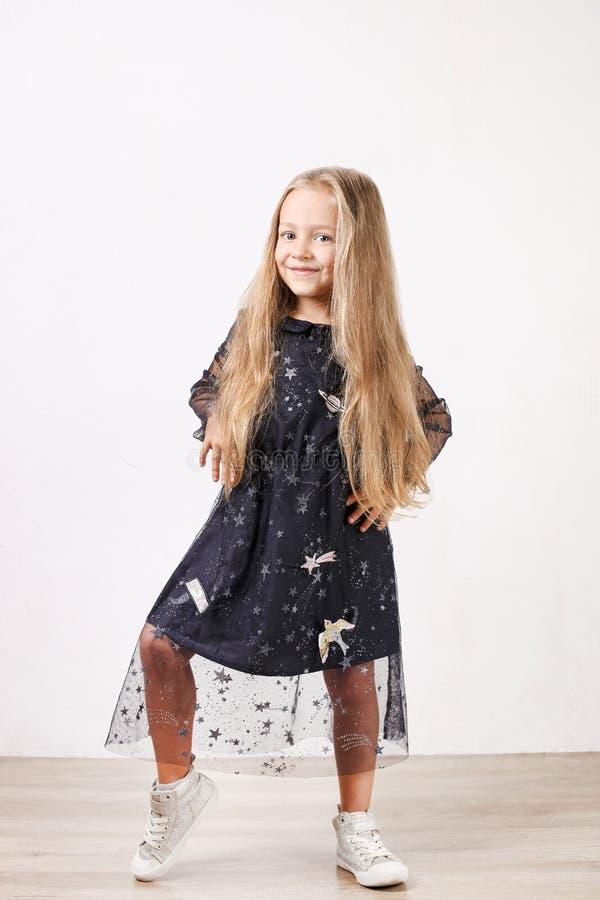 Chica joven divertida linda que presenta en el estudio que muestra la ropa y emociones Fondo blanco aislado foto de archivo