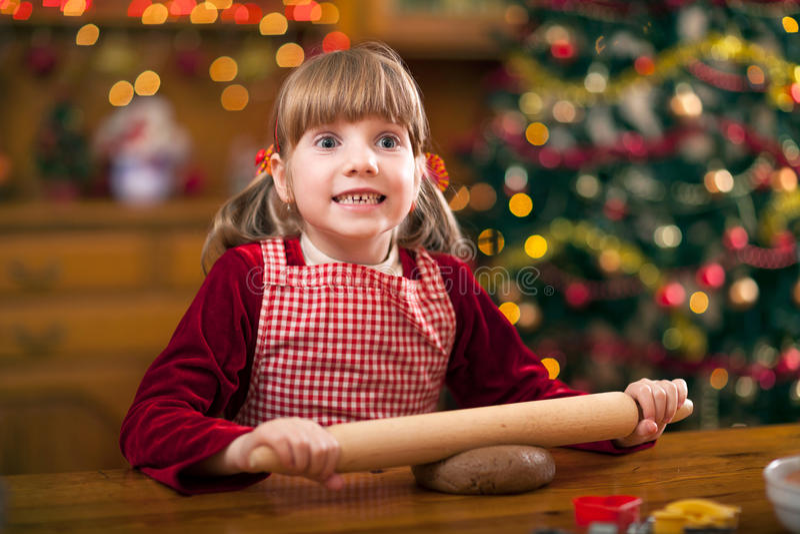 Chica joven divertida que prepara las galletas en Navidad fotografía de archivo