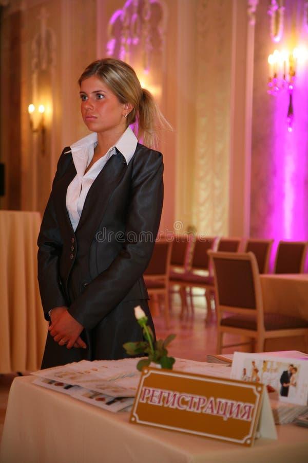 Chica joven - el encargado del restaurante saluda a huéspedes con un banquete festivo Bienvenido foto de archivo libre de regalías