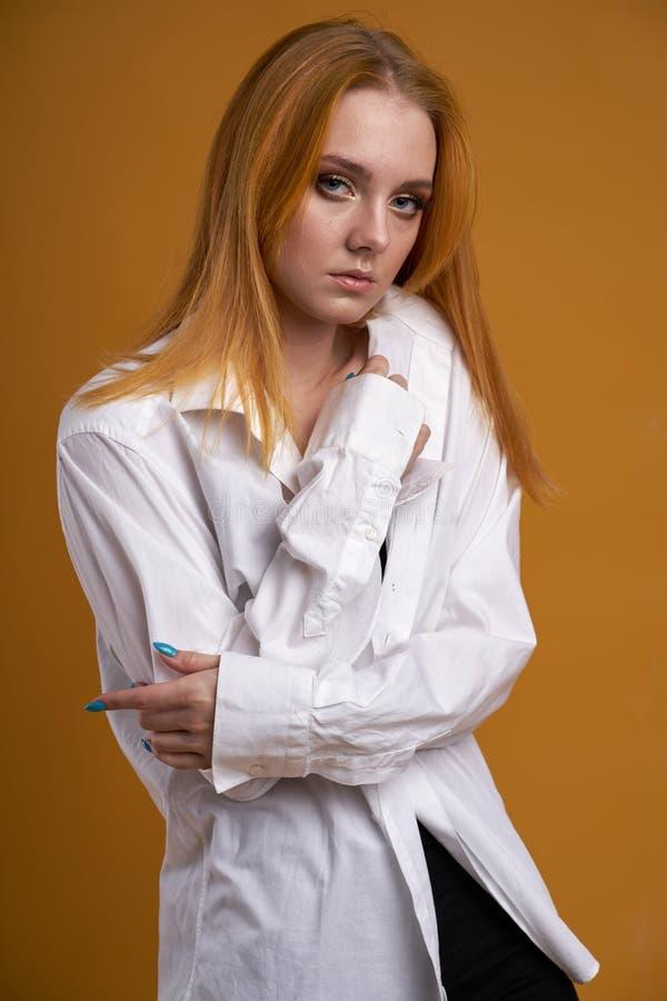 Chica joven elegante con el pelo rizado, sonriendo lindo, presentando, en fondo amarillo foto de archivo