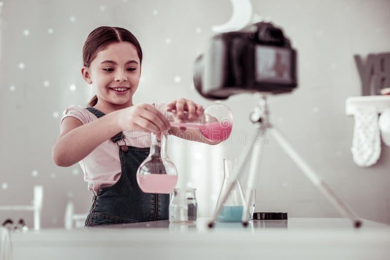 Chica joven elegante positiva que mezcla diversos líquidos foto de archivo libre de regalías