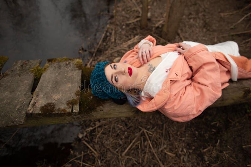 Chica joven elegante que descansa sobre la orilla del r?o, mintiendo en un peque?o puente de madera foto de archivo libre de regalías