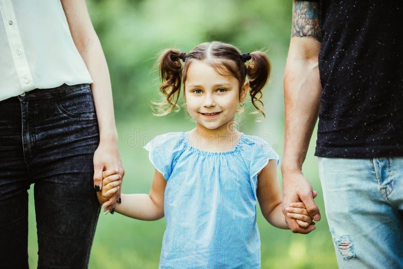 Chica joven emocionada que lleva a cabo las manos mientras que camina con los padres en parque del verano fotos de archivo libres de regalías