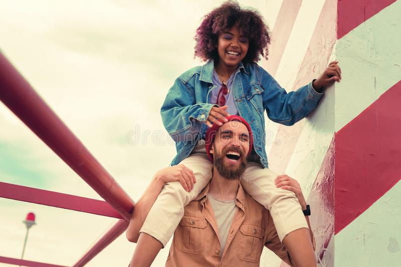 Chica joven emocionada que se sienta en los hombros de su novio y sonrisa confiables imagenes de archivo