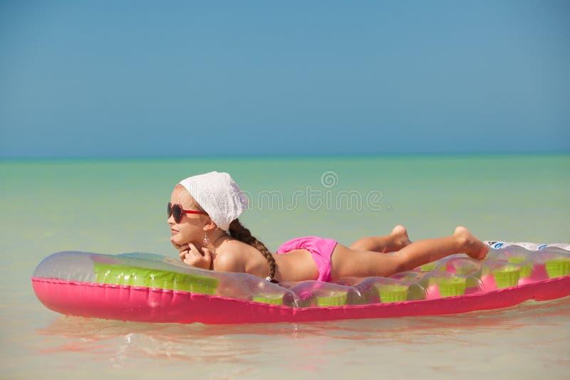 Chica joven en aire-cama rosada en vacaciones del Caribe imagen de archivo