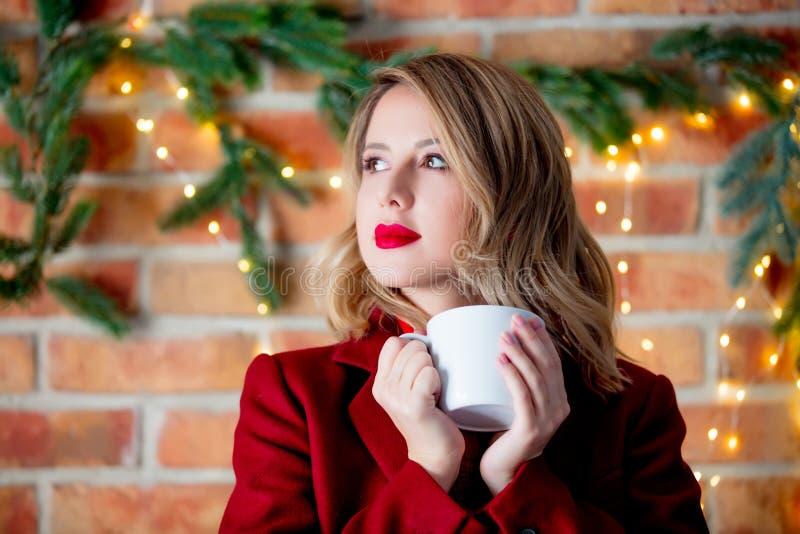 Chica joven en capa roja con la taza de café imagen de archivo