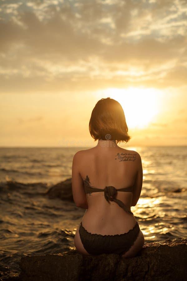 Chica joven en el bikini que se sienta en una roca en una playa imagen de archivo