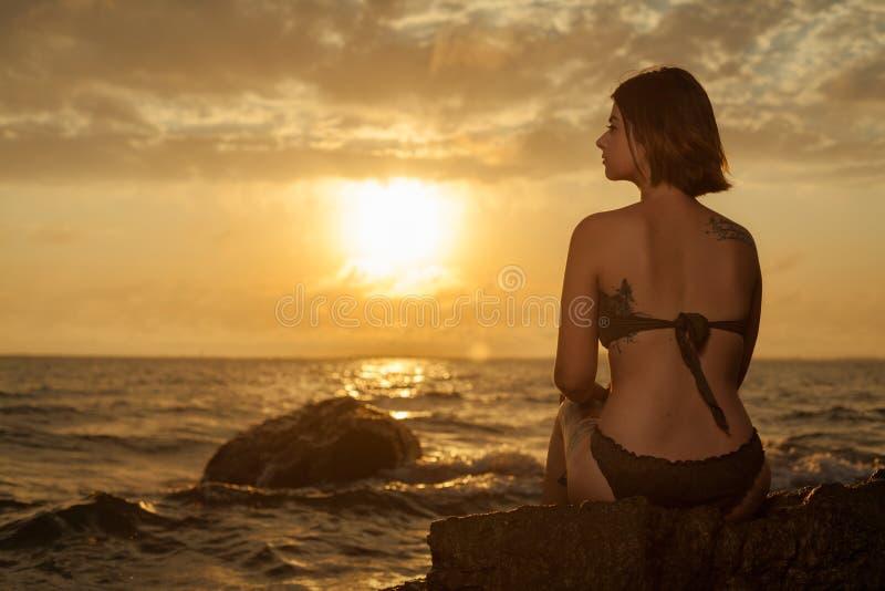 Chica joven en el bikini que se sienta en una roca en una playa imágenes de archivo libres de regalías