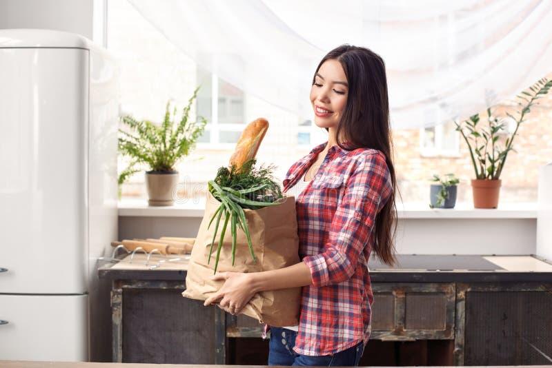 Chica joven en el bolso que lleva de la situación sana de la forma de vida de la cocina con la sonrisa del pan y de las verduras  imagen de archivo libre de regalías