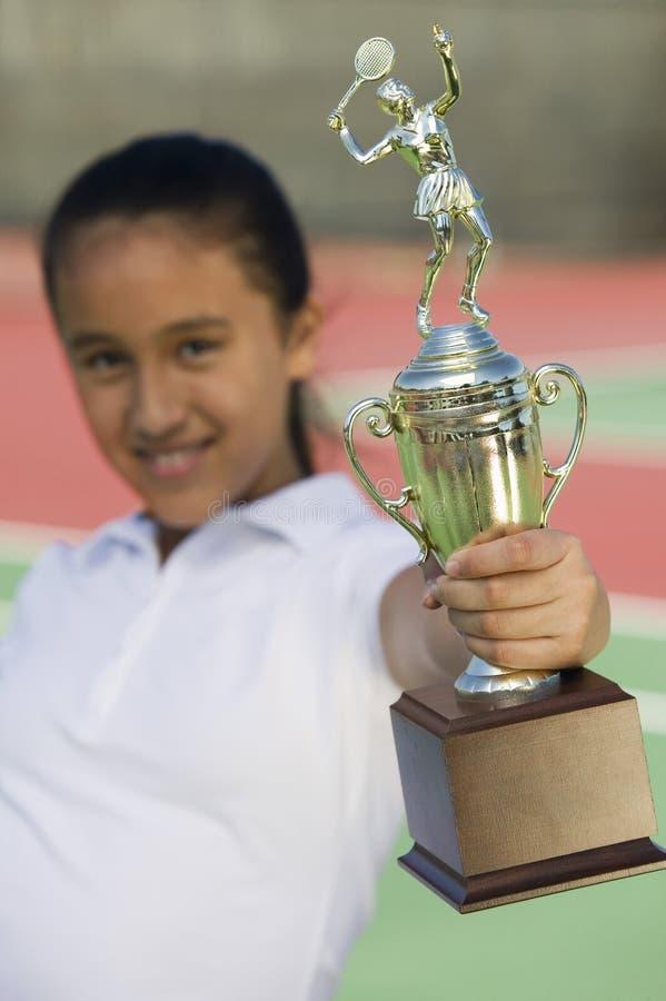 Chica joven en el campo de tenis que lleva a cabo el foco del trofeo en el trofeo imágenes de archivo libres de regalías
