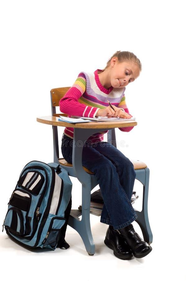 Chica joven en el escritorio en escuela en blanco fotografía de archivo