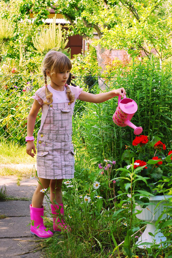 Chica joven en el jardín con la poder de riego fotos de archivo