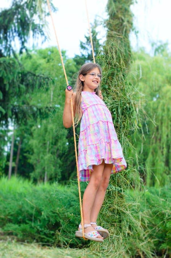 Chica joven en el oscilación fotografía de archivo