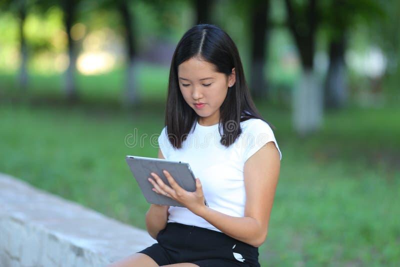 Chica joven en el parque que aprende con la tableta fotos de archivo libres de regalías