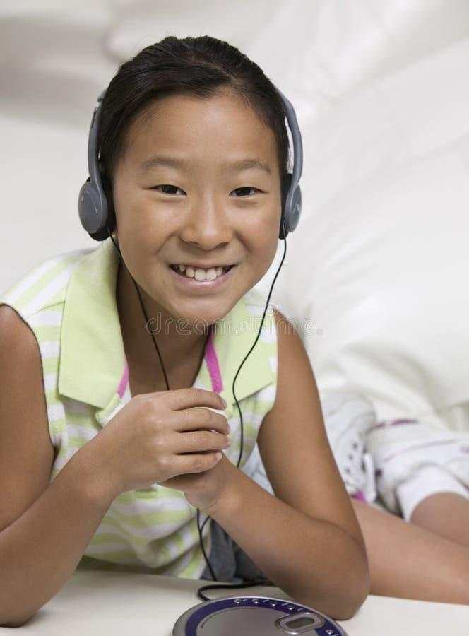 Chica joven en el sofá que escucha el reproductor de CD portátil imagenes de archivo