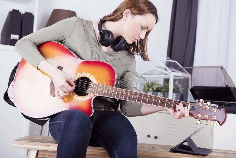 Chica joven en el sofá que toca la guitarra foto de archivo