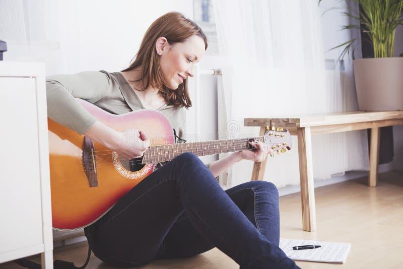 Chica joven en el sofá que toca la guitarra fotos de archivo