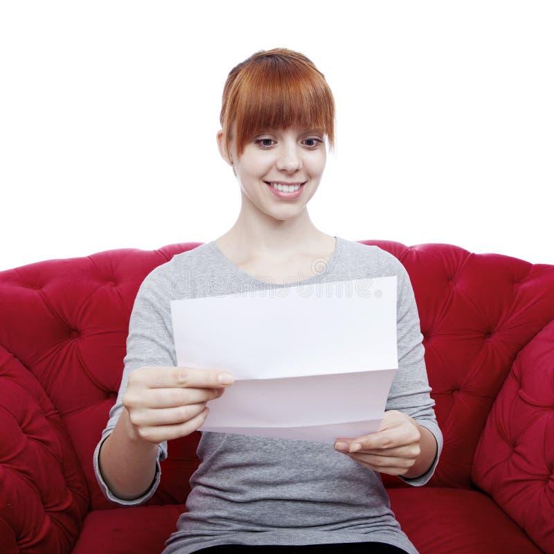 Chica joven en el sofá rojo que lee una letra fotos de archivo libres de regalías