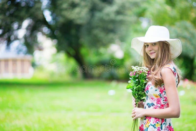 Chica joven en el sombrero blanco que sostiene las flores imagen de archivo libre de regalías