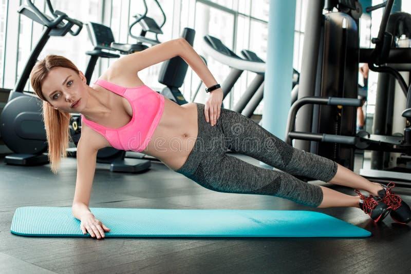 Chica joven en forma de vida sana del gimnasio en la estera que hace el tablón lateral concentrado foto de archivo