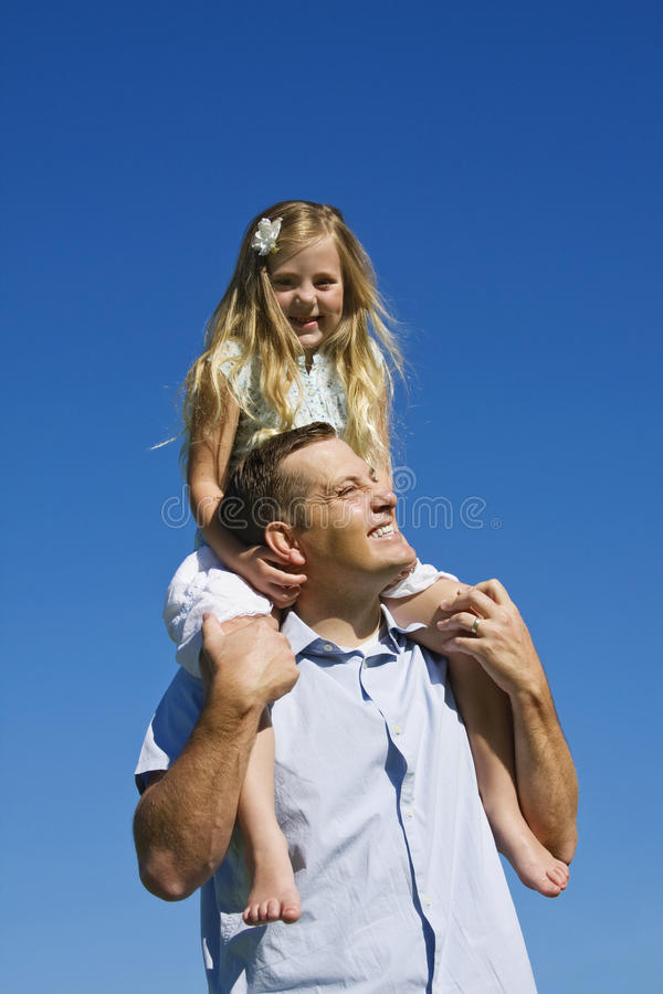 Chica joven en hombros de los padres foto de archivo