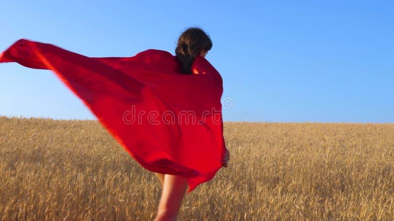Chica joven en juegos rojos del impermeable en funcionamientos del super héroe a través del campo del trigo amarillo contra un ci fotografía de archivo