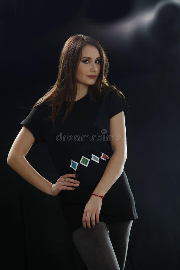 Chica joven en la camiseta negra que presenta en el estudio, llevando a cabo sus manos en la cintura en fondo negro fotos de archivo