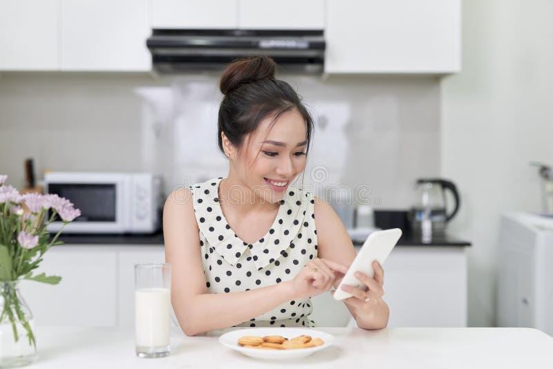 Chica joven en la cocina con el teléfono, el desayuno con leche y las galletas imagenes de archivo