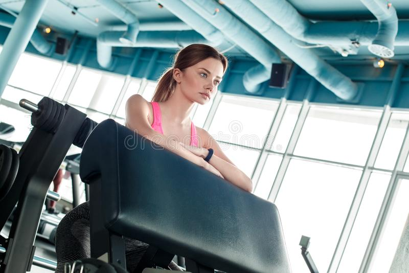 Chica joven en la forma de vida sana del gimnasio que se inclina en el instructor motivado fotos de archivo