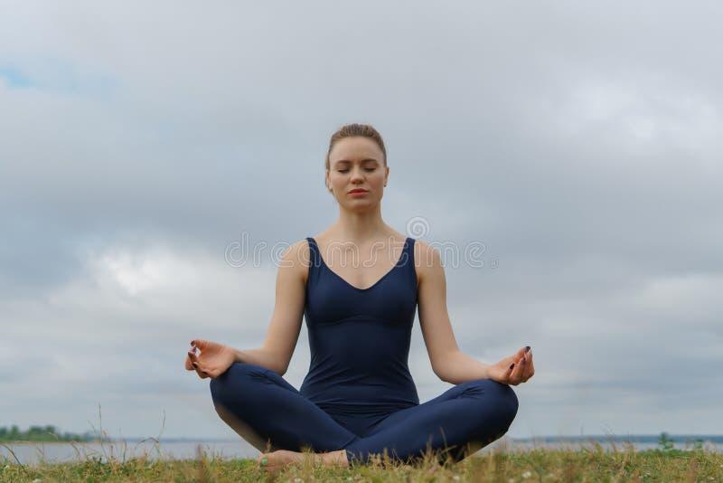 Chica joven en la ropa de deportes azul que se sienta en actitud de la yoga, cielo nublado y el lago en fondo fotografía de archivo