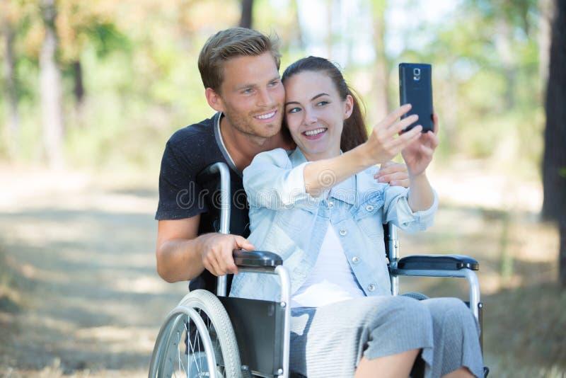 Chica joven en la silla de ruedas que toma el selfie con el novio fotos de archivo libres de regalías