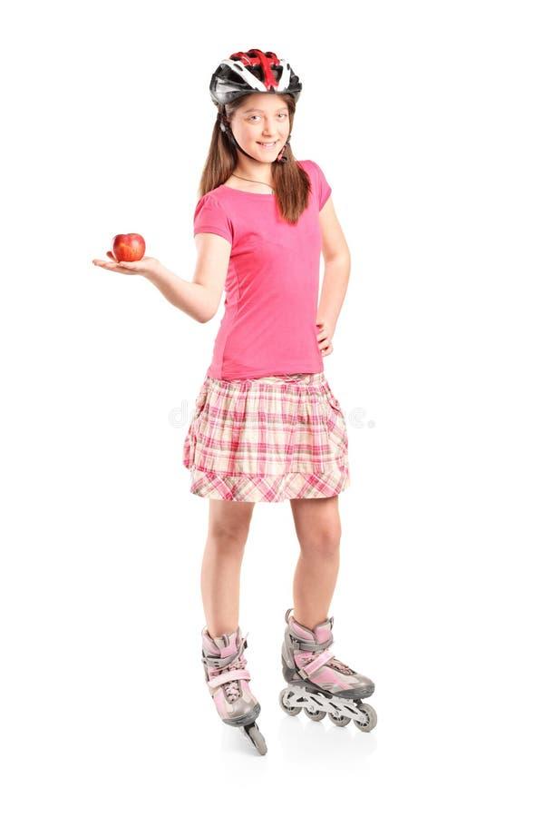 Chica joven en los pcteres de ruedas que sostienen una manzana imagenes de archivo