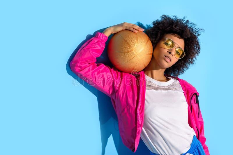 Chica joven en los vidrios que sostienen la bola del baloncesto y que miran la cámara en azul foto de archivo libre de regalías