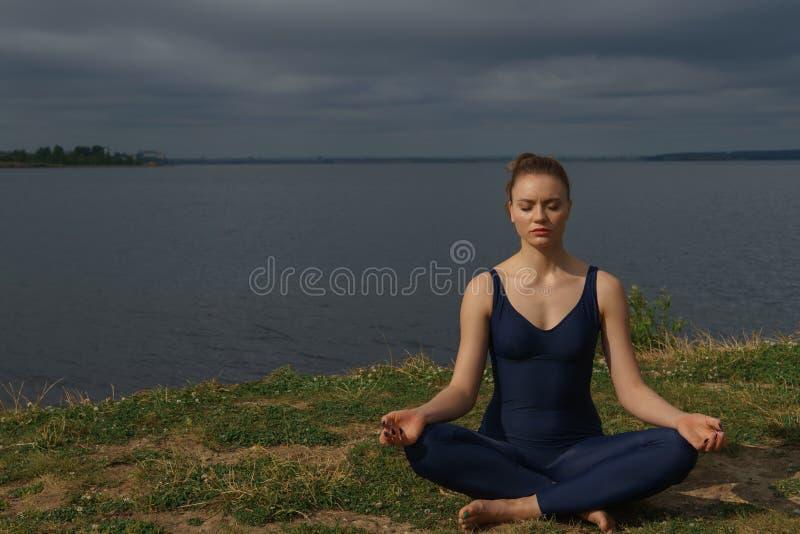 Chica joven en meditar azul de la ropa de deportes al aire libre imagenes de archivo