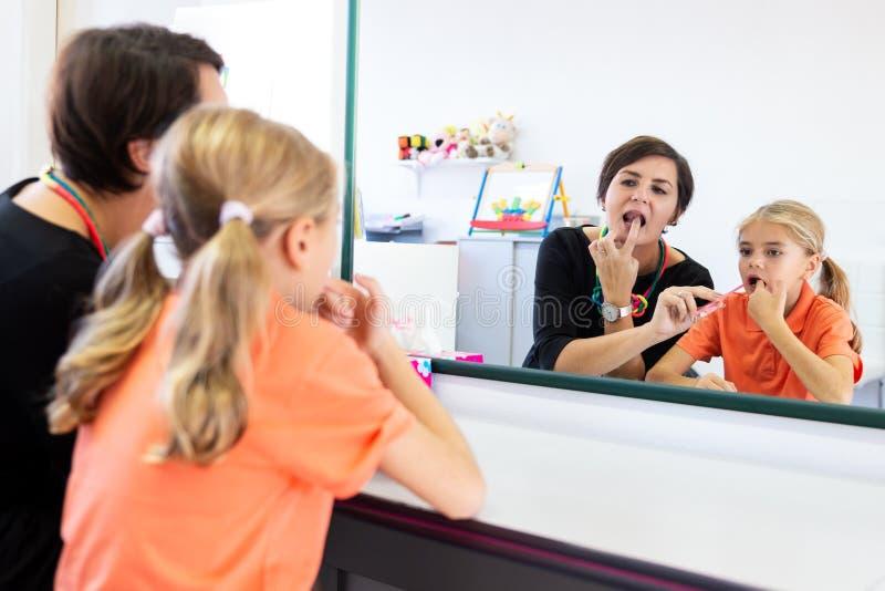 Chica joven en oficina de la logopedia Reflexi?n de espejo de la chica joven que ejercita la pronunciaci?n correcta con el terape fotos de archivo