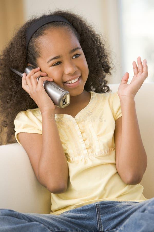 Chica joven en sala de estar usando el teléfono foto de archivo libre de regalías