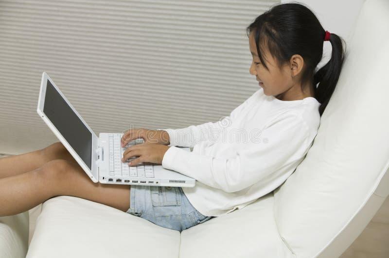 Chica joven en silla usando vista lateral del ordenador portátil fotografía de archivo libre de regalías