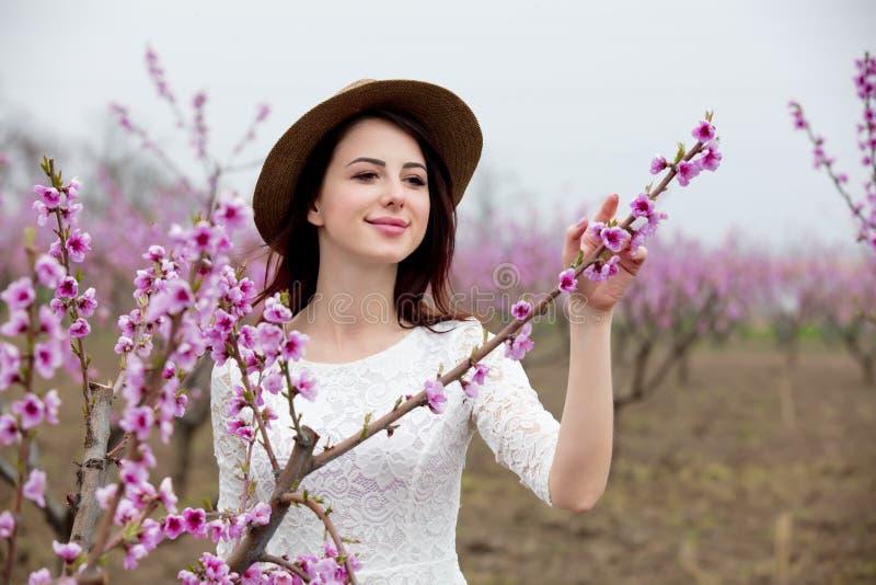 Chica joven en sombrero cerca del árbol de melocotón del flor fotos de archivo libres de regalías