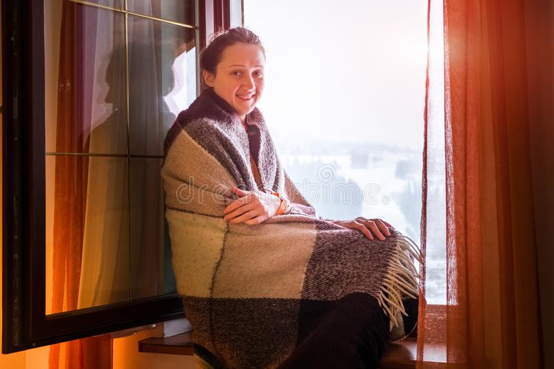 Chica joven en tela escocesa en un travesaño de la ventana en invierno fotos de archivo